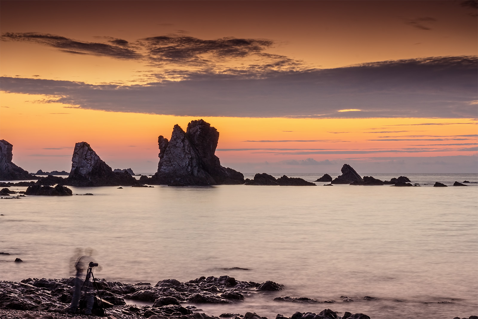 Paisaje con fotografo en la playa del silencio en Asturias. Atardecer