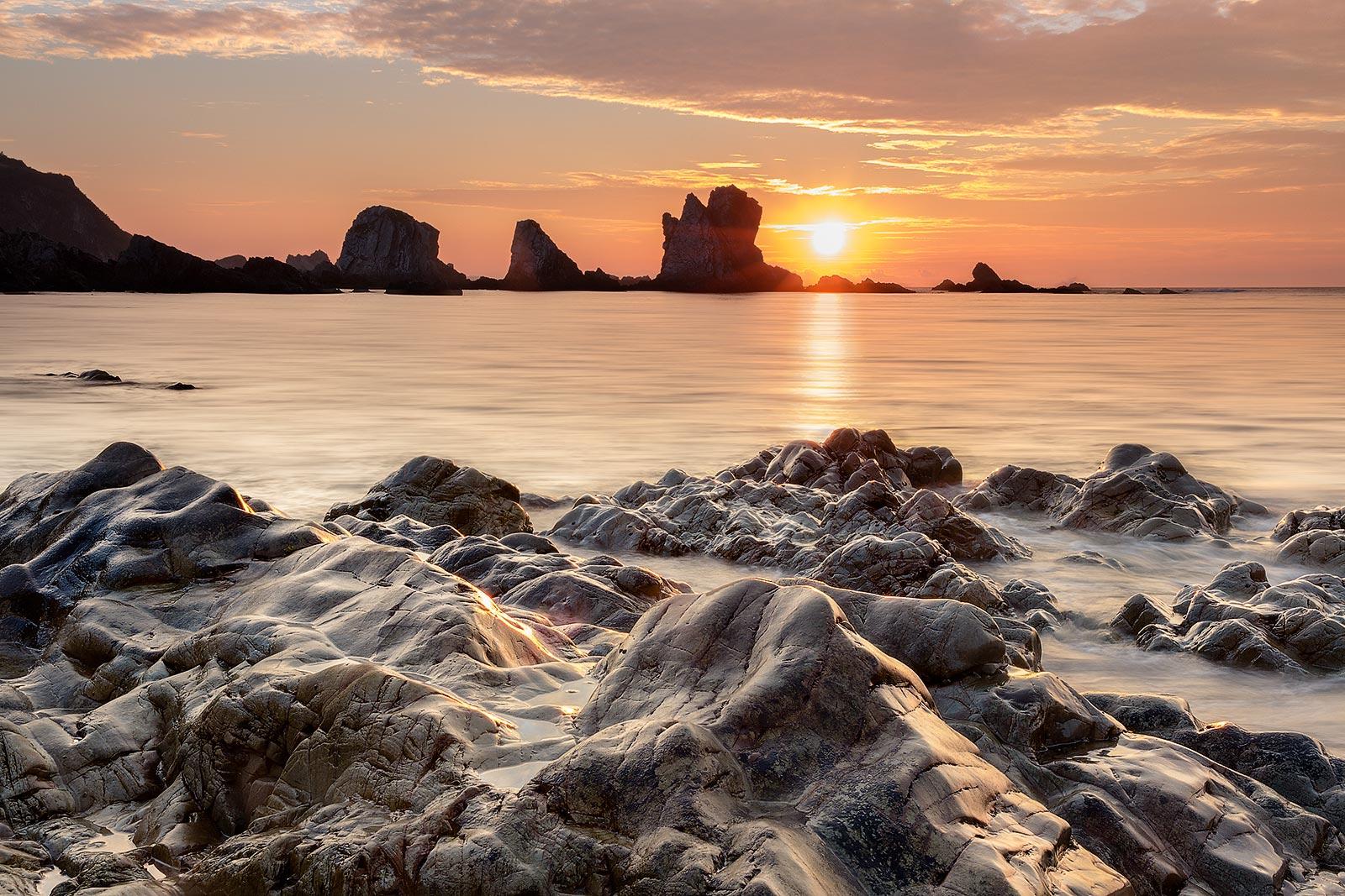 Paisaje atardecer, puesta de sol en la playa del silencio en Asturias, larga exposición